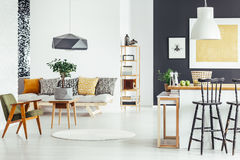 Multifunctional interior with green chair. Bar stool at kitchen countertop in multifunctional interior with green chair and sofa royalty free stock photos