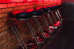 Bar stools at the counter in neon light. leather chairs at the bar in the nightclub royalty free stock photo