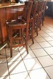 Bar stools lined up at bar. Stock Photos
