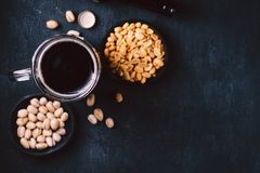 Bar table. dark craft stout beer and snacks set. Bar table. dark beer and snacks set. restaurant, pub, food concept. delicious drink and salty peanuts royalty free stock image