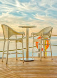 Bar table and two bar stools on the deck at sunset Royalty Free Stock Photos