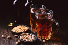 Bar table. two mugs of lager beer and snacks set. Restaurant, pub food. delicious drink and salty nuts. oktoberfest atmosphere, craft brewery concept royalty free stock photo