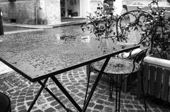 Bar table under the rain. Black and white image. Detail of a bar table under the rain, in the old Italian city centre Stock Photography