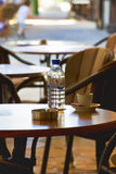 Bar tables. Water bottle, coffee cup and saucer and ashtray on a bar table Stock Image