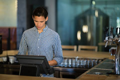 Bar tender operating cash desk at counter. In restaurant Royalty Free Stock Image