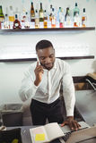 Bar tender talking on mobile phone at bar counter. In restaurant Royalty Free Stock Images