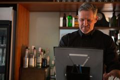 Bar tender using desktop pc Stock Image