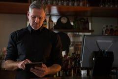 Bar tender using digital tablet. At bar counter Stock Photography
