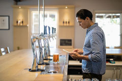 Bar tender using digital tablet at counter Stock Images