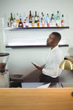 Bar tender writing on a clipboard at bar counter. In restaurant Royalty Free Stock Photo
