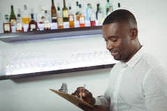 Bar tender writing on a clipboard at bar counter. In restaurant Royalty Free Stock Photos