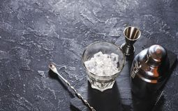 Bar tools for making cocktail. Shaker and a glass of ice on dark stone table. royalty free stock images