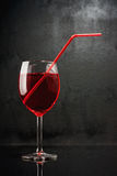 In a bar of vampires. Cocktail on the basis of blood. A glass with a red liquid and red pipe on black grunge background Stock Photography