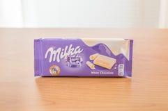Bar van Milka White Chocolate op houten lijst stock foto