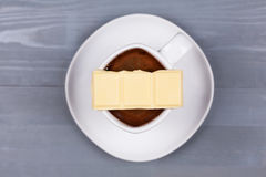 Bar of white chocolate on cup of coffee or milk. Royalty Free Stock Image