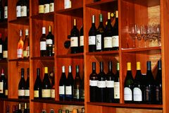 Bar and wines on shelves. Facade of a restaurant bar and various bottles of wines on shelves Royalty Free Stock Images