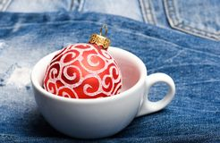 Bar winter season cocktail menu. Winter hot drink concept. Ceramic cup or mug with christmas ball ornament inside on. Denim background. Celebrate new year drink royalty free stock photo