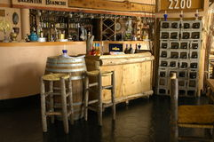 Bar. Wodden bar with rustic stools and a wooden barrel Royalty Free Stock Photos