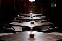 Bar wooden tables in a row, with pepper, salt shaker, toothpicks, wipes stock images