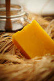 Bar of yellow soap. Nestled in straw with a jar in the background Stock Photos