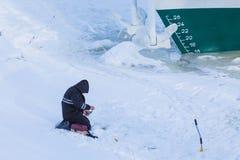 Bara fiskaren som sitter på isen och snön av vinterfloden på bakgrunden av skeppet arkivfoto