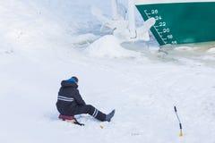 Bara fiskaren som sitter på isen och snön av vinterfloden på bakgrunden av skeppet med ankaret royaltyfria bilder