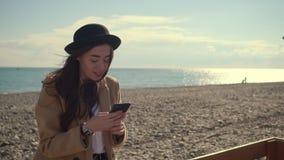 Bara pratar den nätta damen direktanslutet genom att använda radion i smartphone i havsstrand arkivfilmer