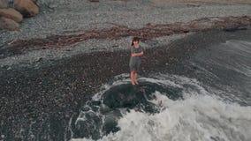 Bara står kvinnan på kusten lager videofilmer