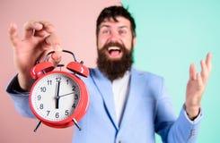 bara tid För affärsmanhåll för man skäggig lycklig gladlynt ringklocka Begrepp i rätt tid Lycklig arbetsdagsär för hipsteren över royaltyfria foton
