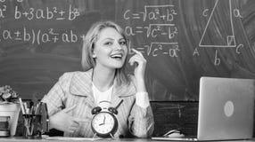 bara tid l?rare med ringklockan p? svart tavla Tid Kvinna i klassrum tillbaka skola till L?raredag Studie och royaltyfri fotografi