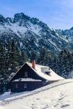Baracca di legno nelle montagne coperte di neve immagini stock