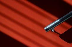 Barandilla inflexible con las sombras en la pared roja Fotos de archivo libres de regalías