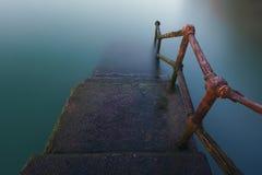 Barandilla oxidada que va abajo en el agua Fotografía de archivo libre de regalías