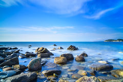 Baratti bay, rocks in a blue ocean on sunset. Tuscany, Italy. Royalty Free Stock Photos