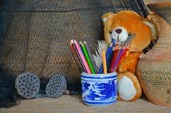 Barattoli ceramici delle matite colorate con la bella bambola Fotografie Stock Libere da Diritti