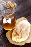 Barattoli del favo dell'ape del miele e del polline dell'ape sulla tavola di legno con il favo della cera Fotografia Stock Libera da Diritti