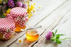 Barattoli del mazzo delle erbe curative e del miele sulla tavola Fotografia Stock