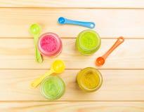 Barattoli del purè differente del bambino e del cucchiaio dimensionale di colore su legno leggero Immagini Stock Libere da Diritti