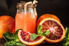 Barattoli del succo fresco dell'arancia sanguinella, fuoco selettivo Immagini Stock