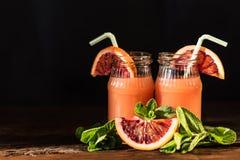 Barattoli del succo fresco dell'arancia sanguinella, fuoco selettivo Fotografia Stock