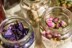 Barattoli delle foglie di tè e dei fiori secchi Fotografie Stock