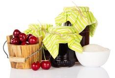Barattoli di inceppamento e del secchio di legno con le ciliege Immagini Stock