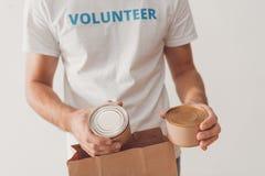 Barattoli di latta mettenti volontari in sacco di carta Fotografie Stock Libere da Diritti