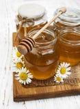 Barattoli di miele con la camomilla Fotografia Stock
