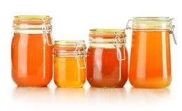Barattoli di miele su bianco Fotografie Stock