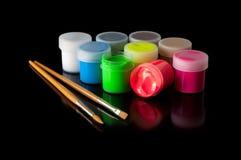 Barattoli di plastica con le pitture acriliche e spazzole su fondo nero Fotografia Stock Libera da Diritti
