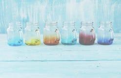 Barattoli di vetro colorati con le maniglie su un fondo blu di legno Fotografia Stock