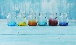 Barattoli di vetro colorati con le maniglie su un fondo blu di legno Fotografie Stock
