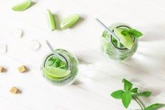 Barattoli di vetro con il cocktail di Mojito sulla tavola di legno bianca Calce slic Fotografia Stock