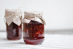 barattoli di vetro con l'inceppamento di lampone su una tavola di legno, preparazioni casalinghe, cucinando, dessert casalinghi fotografia stock